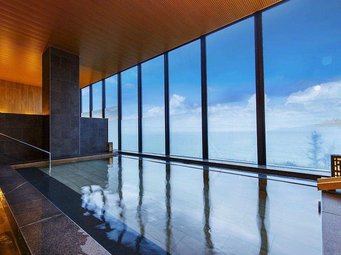 沖縄の青い海と空を一望できる絶景風呂。時間によって魅せる表情は様々で夕景もまた美しい
