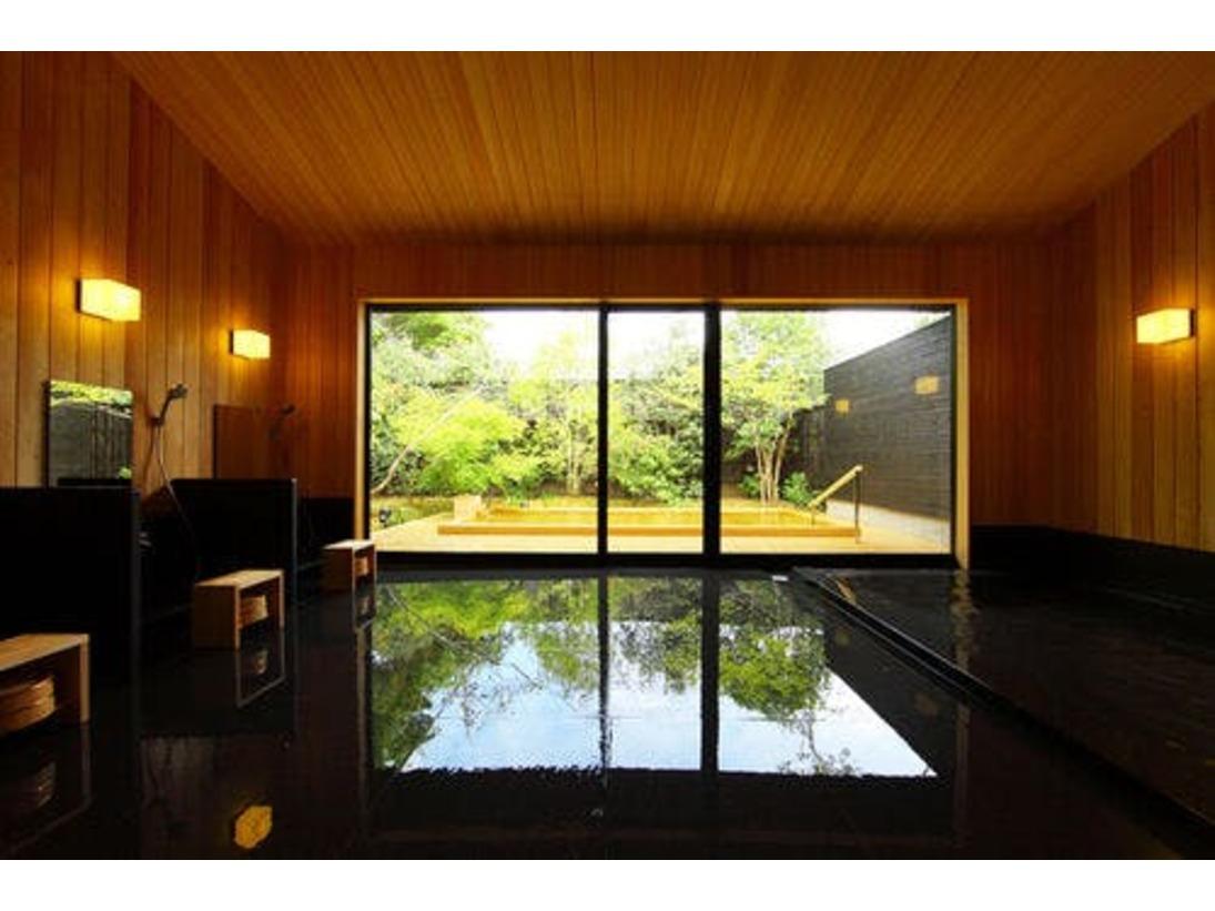 インテリアデザイナーの内田繁氏がデザインした大浴場「風花」。内風呂の浴槽は御影石。檜に囲まれた木々の香りに包まれた空間で湯浴みいただけます。