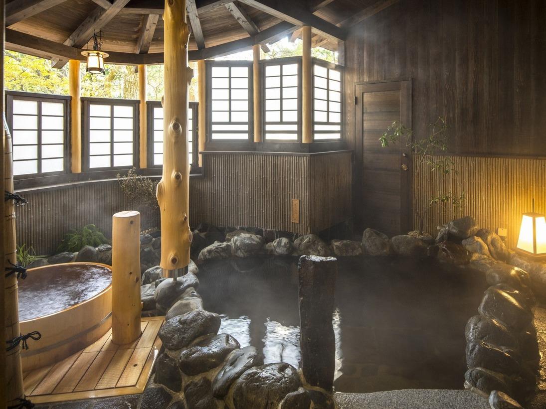 岩造りの半露天風呂。優しい灯篭の光が湯に溶け込み、安らぎの空間を演出する。