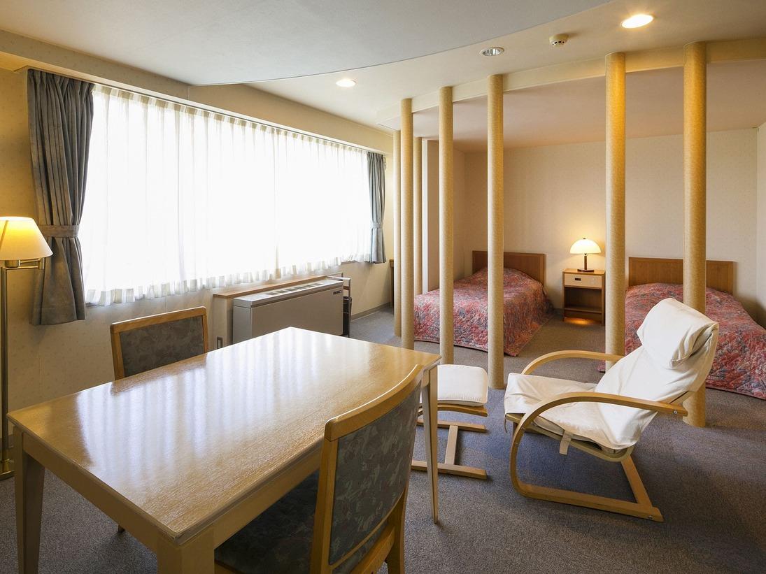 【客室一例】本館ツイン/大きなテーブルや足を伸ばせるチェアなど寛げる設備も充実。
