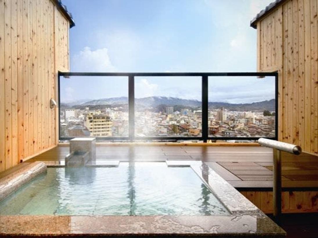 飛騨の町並みと山並みを一望する客室露天風呂(例)。