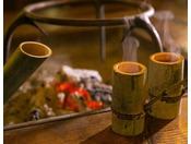 【館内施設】囲炉裏を囲んでいただく闊歩酒。青竹の油分が酒にしみ出て独特の風味に、笑顔がこぼれます。