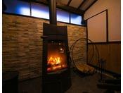 【館内施設】薪ストーブの前で温まりながら過ごす、ゆったりとした時間。沈黙さえも心地よく感じられます。