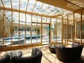 リゾート感溢れる屋内温水プールサイドのラウンジ