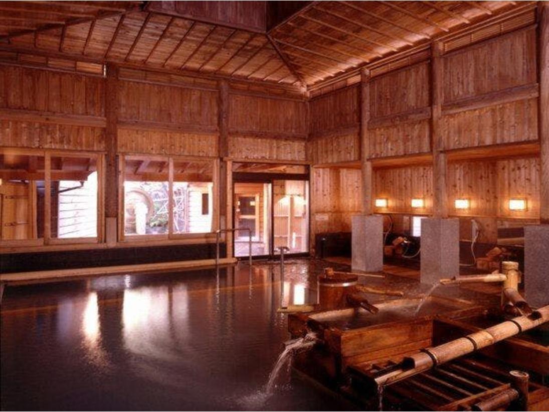 【大浴場:鷹の湯】宮大工による伝統の湯屋建築造りの大浴場。昼間でも薄暗いその独特の雰囲気は温泉情緒に溢れ、日頃の 疲れをときほぐす癒しの空間です。浴槽は「あつ湯」「ぬる湯」「腰湯」と、温度の違いによって別れています。お好みに合わせてお入りください。