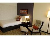 本館20~23階 シングルルーム。ミッドセンチュリー特有の幾何学パターンとダークブラウンの木目調が美しく調和した客室です。ビジネスでのご利用にも最適です。