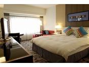 本館20~23階 ダブルルーム。ミッドセンチュリー特有の幾何学パターンとダークブラウンの木目調が美しく調和した客室です。高層階から港町を一望する眺めもお楽しみいただけます。
