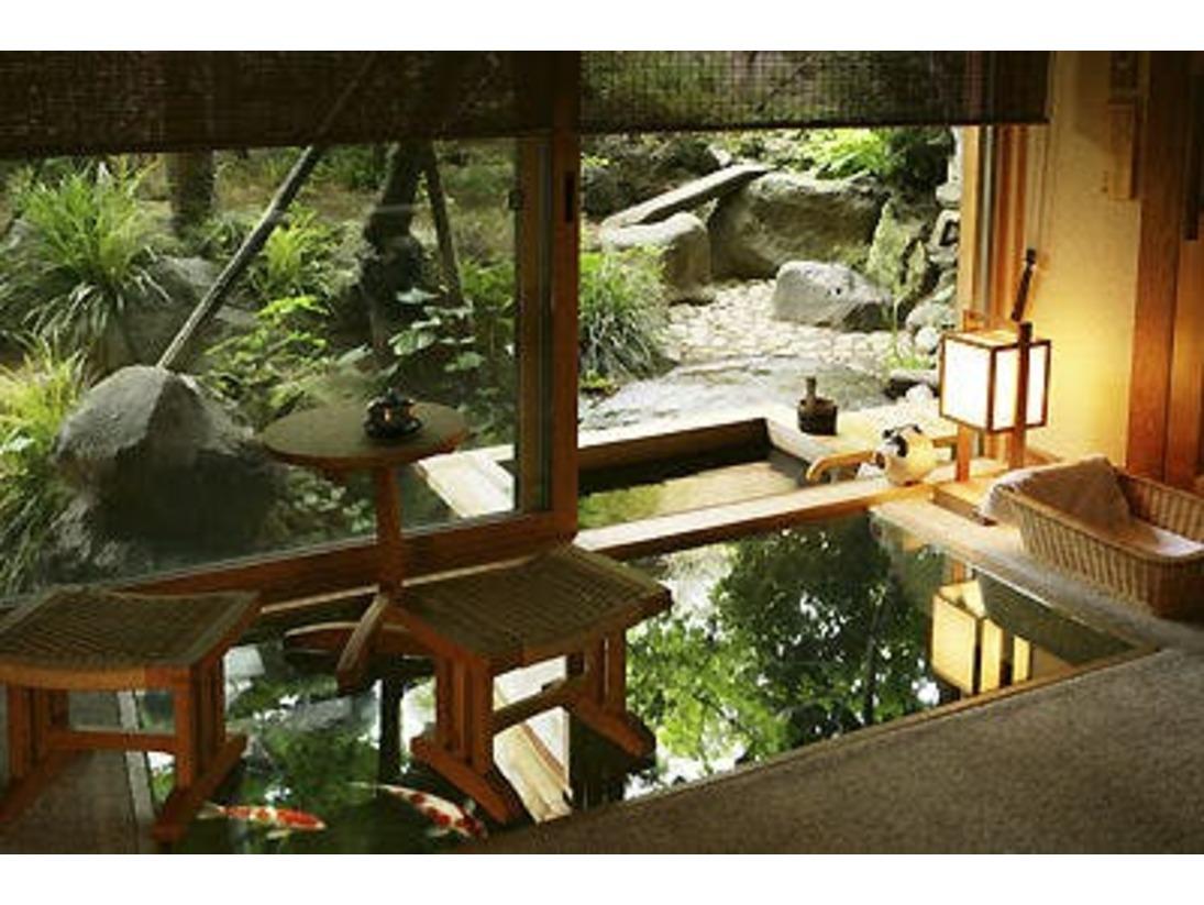 「桂の間」の露天風呂です。湯量豊富な温泉かけ流し総檜露天風呂となっております。広縁のガラス床の下から露天風呂脇に泳ぐ錦鯉を眺めながら、温泉を愉しめます。