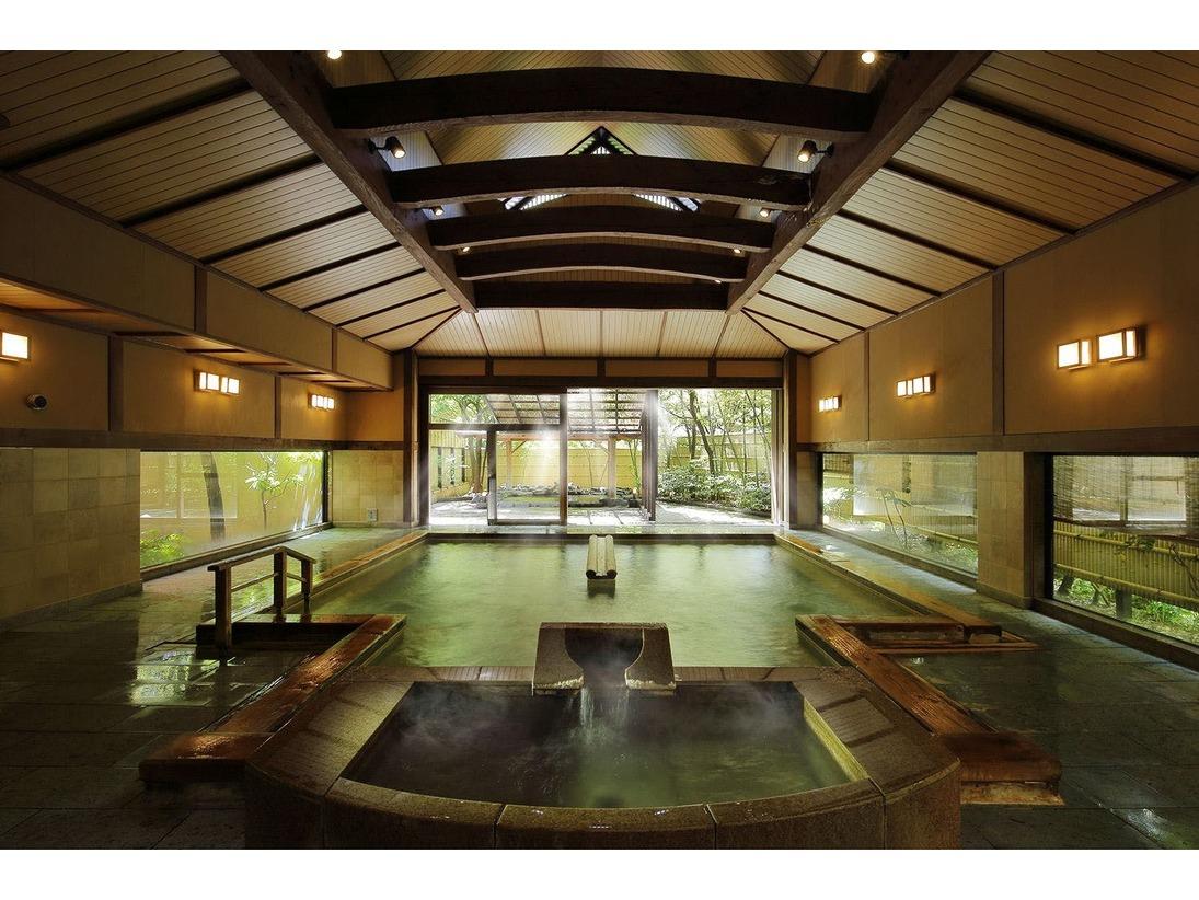 【男性用大浴場】古くから名湯として知られるあつみ温泉。天井が高く、開放的な造りの大浴場に身を委ねれば、まろやかなお湯が体を包み込みます。