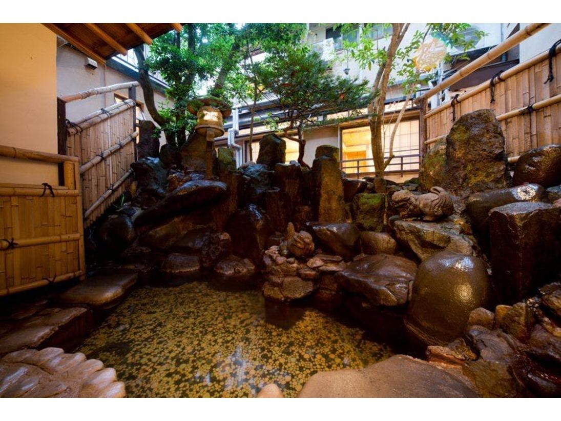 大正時代からの石組みが美しい「石割の湯」。内庭露天の足湯です。