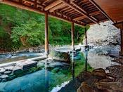 ~新緑のお題目大露天風呂~ 四万川を眼前に臨む岩風呂、説法の彫られた大岩の近くは熱めのお湯です。