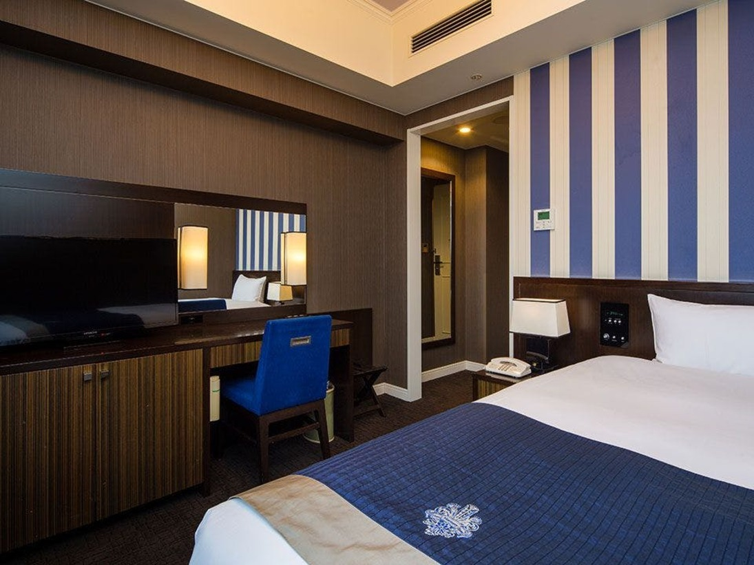 スタンダードシングル京都の落ち着いた雰囲気をチャコールグレーと濃紺ストライプのコントラストで表現した印象的なお部屋です。ルームサイズ|18平米ベッドサイズ|120×203