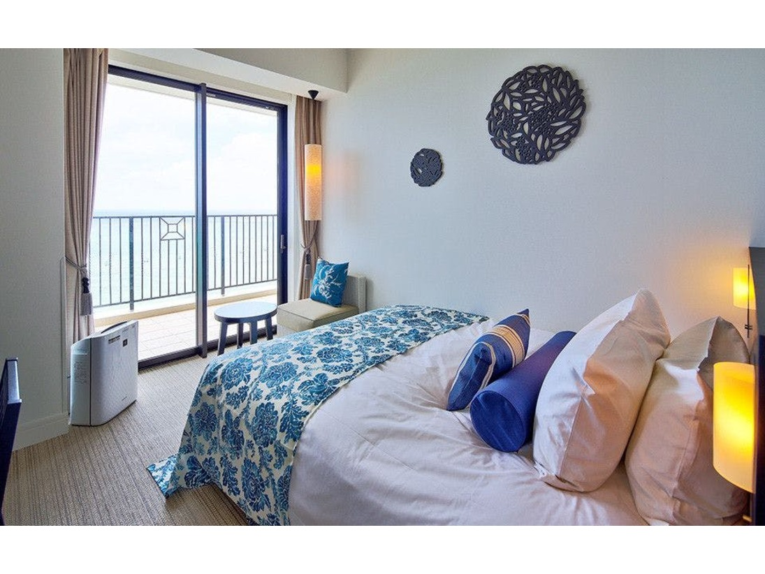 【ダブル】ホワイトとブルーのコントラストのデザインの客室は、リゾートホテルらしくリフレッシュできる雰囲気をかもし出します。ベッドからは寝そべったまま沖縄の空と海をご覧いただけます。※バスルームはユニットタイプとなります(客室一例)