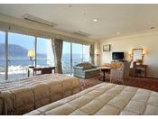 デラックスツインルームでございます。広さは、43.5平方メートル。窓からは雄大な桜島をご覧いただけます。