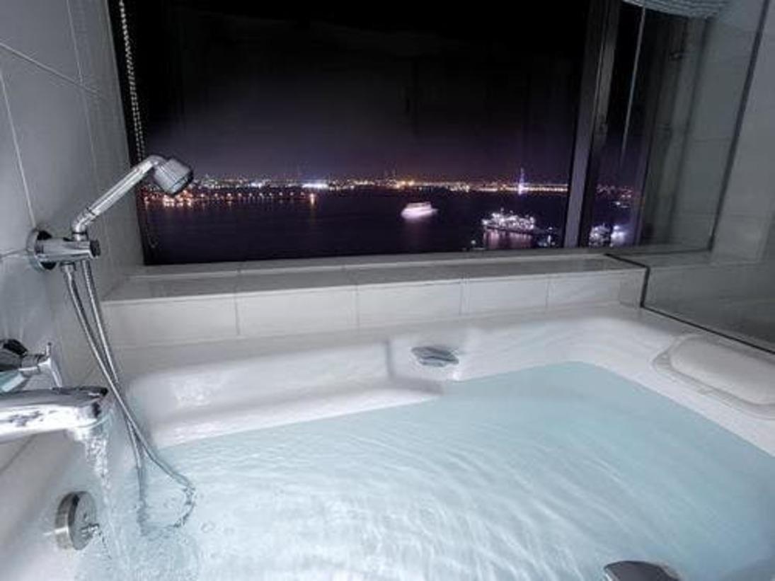 ホテル先端に位置するスイートではバスルームからも夜景を望めます。ベイブリッジや埠頭のやわらかな灯りに照らされた横浜港の景色をお楽しみください。