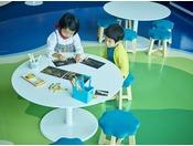 <アクティビティラウンジ>フロントから見下ろすと伊豆七島のグラフィックを配したワークショップを行うステージやテーブル、島のようなベンチシートがブルーの床に点々と浮かんでいます。