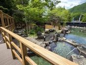 【大露天風呂HOSHI★ZORA】まるで庭園のような石造りの露天風呂と木々。(ガウンの貸出しあり)