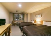 スタンダードツイン滝の湯川が目の前に流れるツインベッドのお部屋。川のせせらぎを感じられる、清涼感あふれるお部屋です。