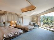 デラックスツインルーム一例。音信川を左右に見渡すコーナールーム。天井から続く大きな窓の外には、渓流と手付かずの自然が広がります。