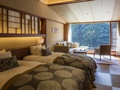 プレミアムツインルームの一例。夏の素足に心地よい琉球畳の上に、シモンズ社製ベッドを備えたツインルーム。窓の外には山々の緑がひろがります
