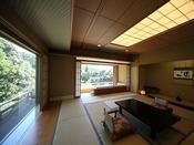 ジャグジー風呂のある和室15帖+広縁(ソファ付)。木々の緑と渓流を近くに感じる角部屋。目の前の窓からは、山間の静かな景観がジオラマのように広がります。のどかな当館でゆっくりと日常を忘れてお過ごしくださいませ(客室一例)