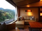 大きな一枚窓からの景観を望む、居心地の良いプレミアムルームのサロン
