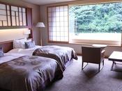 大谷山荘のスタンダードタイプの洋室。幅125cmとセミダブルサイズベッドを2台配置したツインルームです。和の落ち着いた雰囲気と約38平米の広さがございます。窓の外の自然をみながら、ゆっくりと安らぎの時間をどうぞ/客室一例