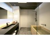 檜葉(ヒバ)の木の浴槽とシャワーブースを備えたユニットバスタイプのバスルーム