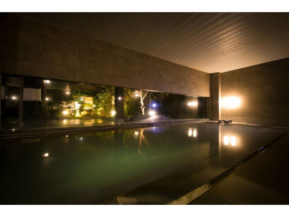 【大浴場】夜になるとライトアップされた日本庭園と白濁したお湯が共鳴し、幻想的な世界を作り出します。
