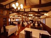 食堂。天井の梁の重厚感、やわらかな橙色の灯りの中での朝食は特別なひととき。