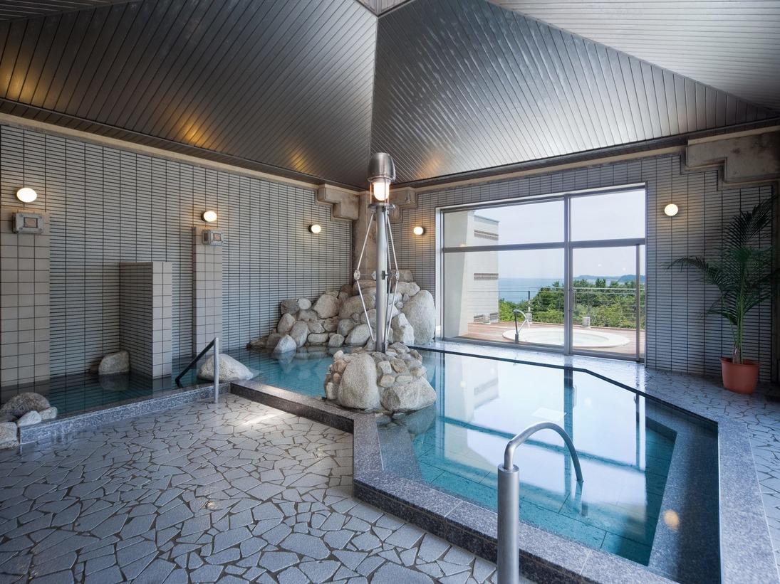 あさなぎの湯の内風呂。日本三大ラジウム温泉として有名な新潟県「栃尾又温泉郷」一帯から産出される、ミネラル等を含有するトゴール鉱石を使用。天然温泉により近い泉質のお湯を人工的に作り出した準天然温泉です。(朝なぎ・夕なぎの湯は、男女入替制です。)