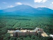 【外観 春~夏】森林と高原の緑に囲まれ、近くに浅間山を臨むロケーション
