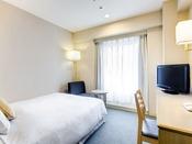 【シングルルーム】シンプルで機能的な客室。140cm幅のダブルベッドでゆったりとおくつろぎ下さい。