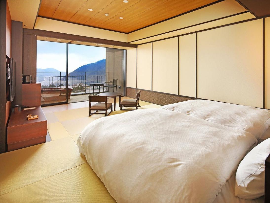 箱根外輪山が広がる、開放感あふれる眺望が魅力の露天風呂付客室。バルコニーには机とイスのセットをご用意。露天風呂は足湯としてもご利用いただけます。
