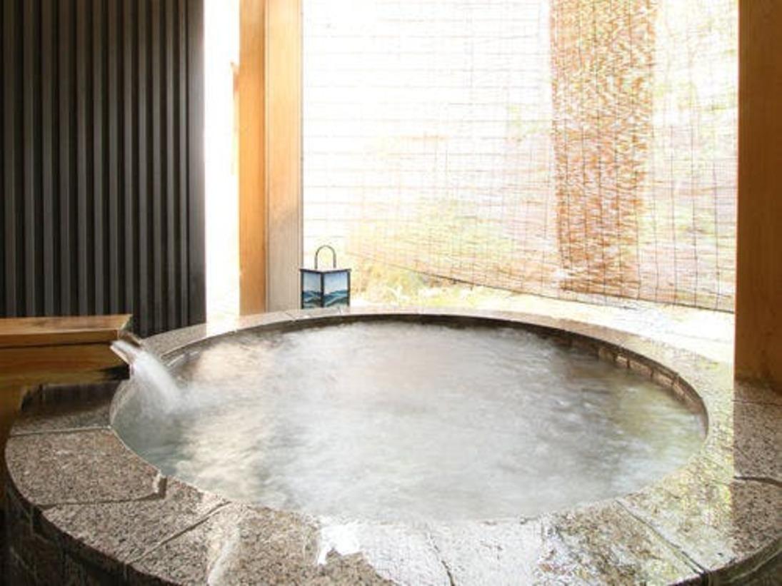 大浴場に併設された庭園を望む石造りの露天風呂。