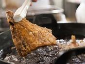 名物のまぐろのカマ唐揚げは低温でじっくり揚げてから継ぎ足しのタレにつけています