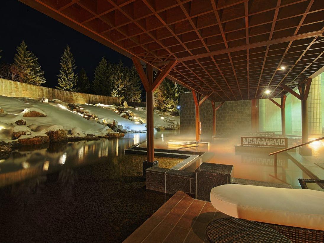 【大浴場 湯楽/1階】庭園露天風呂「森の清流・滝壺の湯」幅約30mのダイナミックな滝の流れを眺めながら入る立湯をお楽しみください。