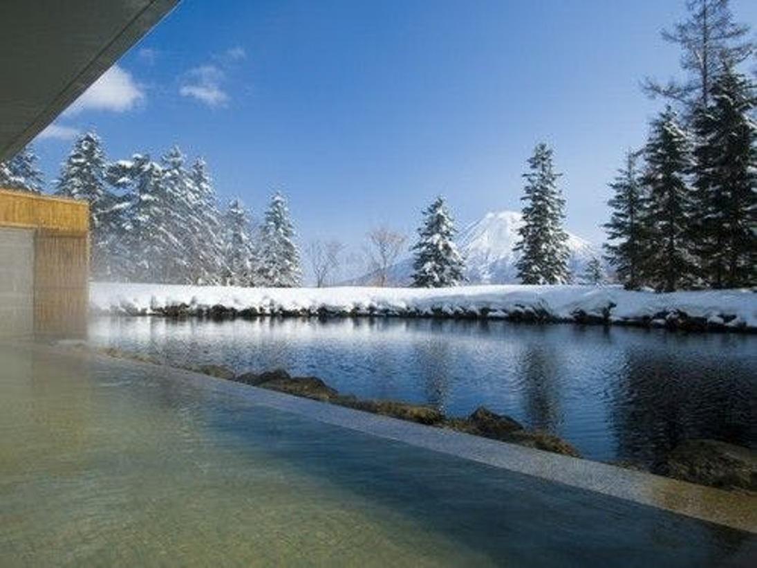 【露天風呂・冬】羊蹄山を望む源泉かけ流し温泉。自家源泉かけ流しの温泉には疲労回復に効果の高い成分が多く含まれており、ゴルフやスキーなどのリゾートアクティビティで疲れた身体を優しく癒します。