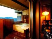 バリアフリー ツインベッドルーム【琥珀】付きの源泉掛け流しの露天風呂。浴槽からは伊東の街並みと相模湾が望めます。