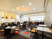 レストラン「グランサンク」白とオレンジを基調とした開放感あふれるレストラン。レストラン内にはキッズスペースがあり、中の様子はモニターからご確認いただけます。