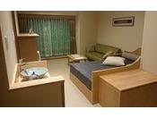 シングルベッド2台と、リビングにはセミダブルのデイベッド1台とソファーも配置した多機能なお部屋