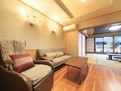 <露天風呂付き客室・湯庵 和室タイプ> 入口側のリビングです。2名掛けのソファーの他、マッサージチェアーも設置しております。壁掛け式のテレビもございますので、室内で分かれてお寛ぎ頂けます。