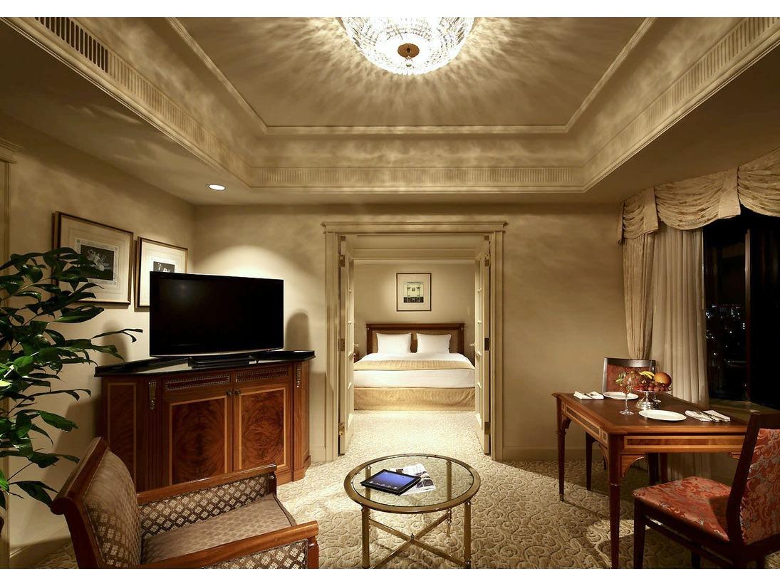 【デラックスフロアー ジュニアスイートルーム ダブル】ソファが並ぶリビングとダブルベッドが置かれた寝室を仕切る白木のドアを開けると、まるでワンルームスイートのような開放感が味わえます。大理石張りのダブルシンクなど、上質感あふれるバスルームも好評です。