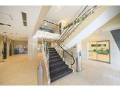 1階正面入り口から入ると階段がございます。2階フロントへは階段、エスカレーターまたはエレベーターをご利用くださいませ。
