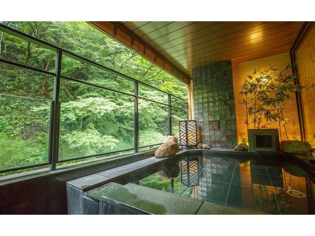 緑が間近に迫る最上階の温泉露天風呂。心地よい自然の声に耳を澄ましながら癒される。