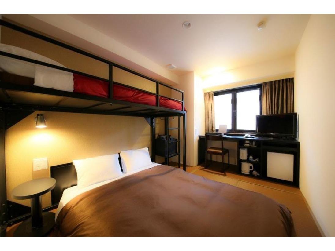 お部屋の広さは15平米。140センチ幅ダブルベッド1台と100センチシングルベッドを2段に設置し、最大3名様まで利用可能にしたファミリータイプのお部屋です。床は畳を敷いており、日本の家族団らんをイメージさせるお部屋です。