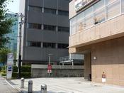敷地内駐車場へは隣NTTデータビルとホテルの間の道をお進みください