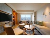 27階に位置するニッコーフロア スイートハリウッドツインルーム(64平米)リビングルームには、ゆったりと寛げるソファをご用意。お部屋から金沢の街並みをお楽しみいただけます。