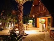 """【ログハウス A-type """"Palm Terrace""""】デッキ中央の大きなナツメヤシが印象的。"""