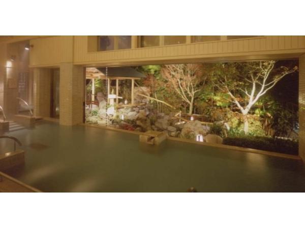 """緑の中に建つ男子大浴場""""天晴""""より庭の左手に段々の湯"""
